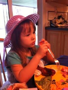 Maddo, her plate full, eyeballs what her sister has across the dinner table.